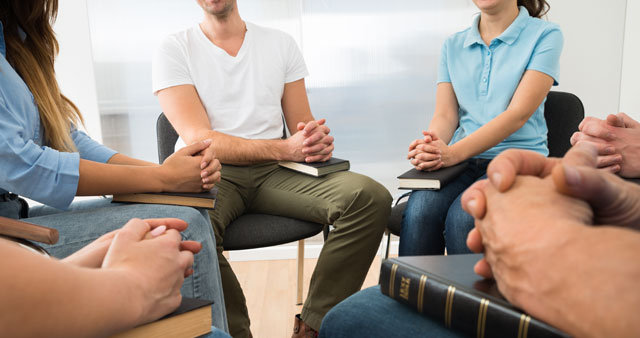 Teenagers sitting in circle praying together